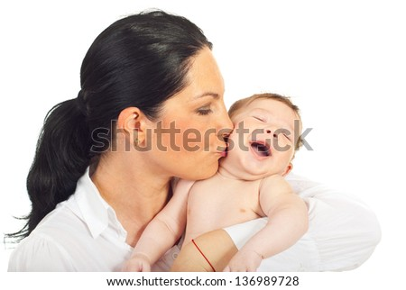 Mother kissing happy newborn baby boy isolated on white background