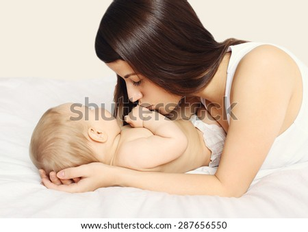 Mother kissing her baby on the bed at home bedtime - stock photo