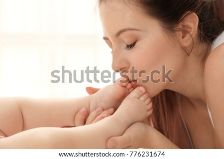 Mother kissing her baby's feet at home