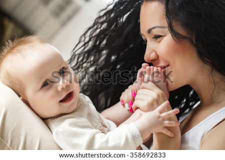 Mother kissing her baby's feet. Mother holding infant's legs. Portrait of a mother with her 4 months old baby at home. Happy child near to mum in her room. Portrait of a mother with her newborn baby.