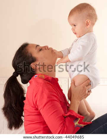 Mother kissing her baby's hand - stock photo