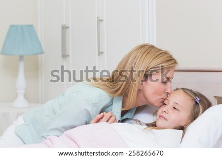 Mother kissing her daughter in the bedroom - stock photo