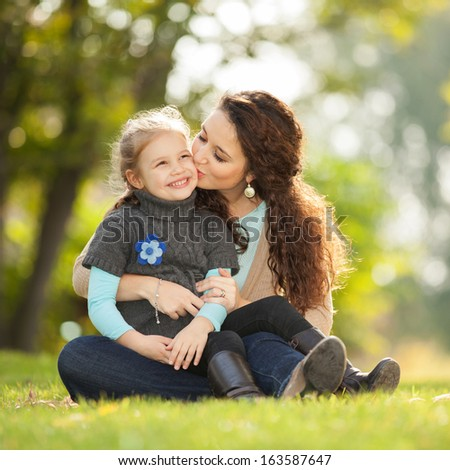 Mother kissing her daughter in the park