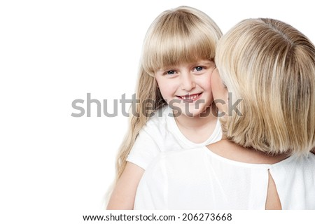 Mother kissing her daughter while daughter posing to the camera - stock photo