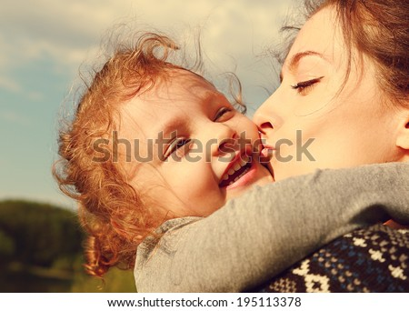 Mother kissing her happy smiling daughter outdoors summer background