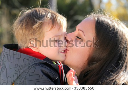 mother kissing her son in a park - stock photo