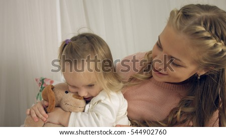 Mother kissing little daughters and their toy