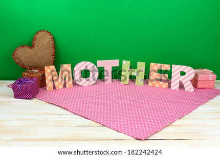 Mother- lettering of handmade paper letters on green background - stock photo