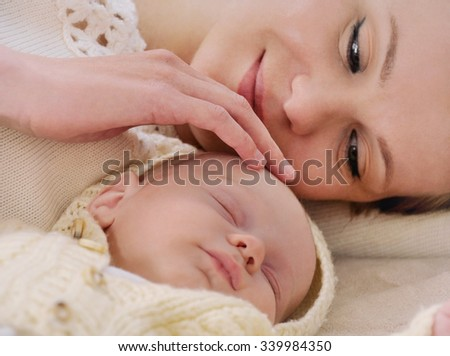 mother lie near the baby and tenderly touching him; softly parent control; sleeping cute baby; maternity concept - stock photo