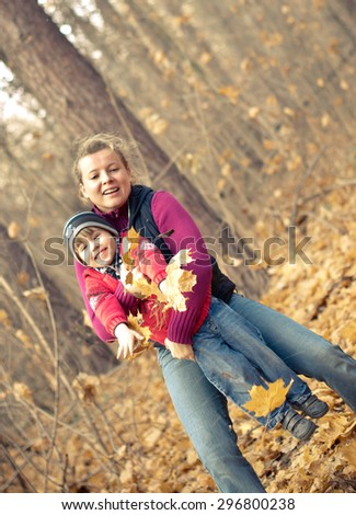 Mother lifting little boy in autumn forrest full of golden leaves