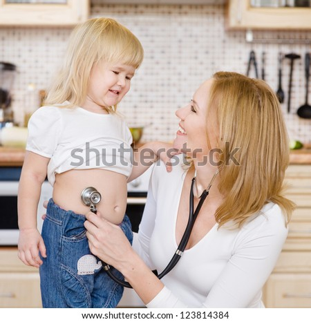 mother listening to  tummy of the daughter - stock photo