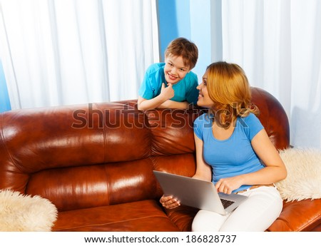Mother looking at her son on sofa with laptop