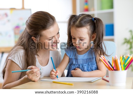 Mother looking how her child daughter drawing a picture - stock photo