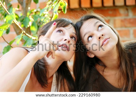 mother looking up and shows her teenage daughter something above - stock photo