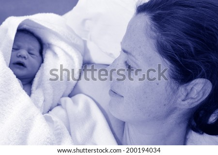 Mother looks at her newborn baby in bed immediately after a natural water birth labour. Concept photo of  pregnant woman, newborn, baby, pregnancy. (BW) - stock photo