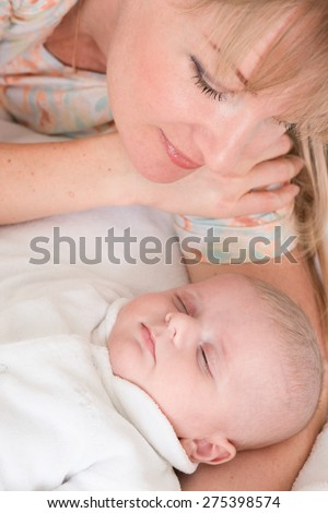 Mother looks at sleeping baby boy