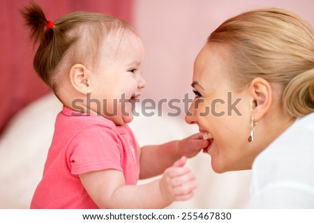 Mother looks with love at baby. Parenthood happiness conception - stock photo