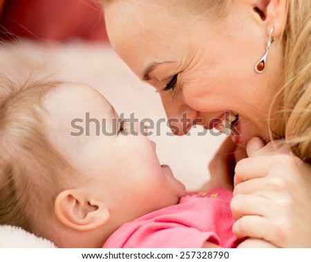 Mother looks with love at child. Parenthood happiness conception. - stock photo