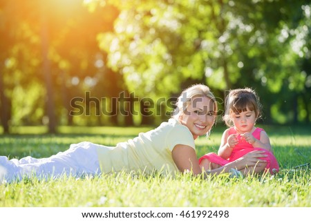 Mother lying on grass while little girl sitting next to her.Sunset park in the background, fens flare, focus on the little girl