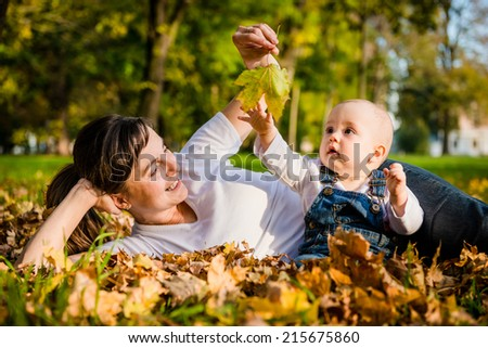 Mother lying with her baby in fallen leaves on beautiful autumn day - stock photo