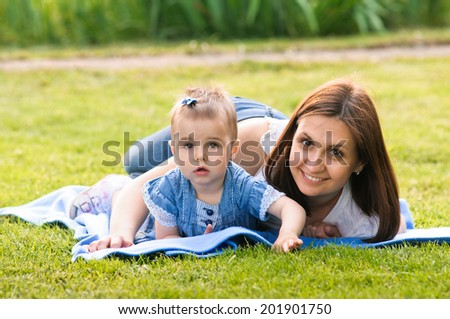mother lying with her little daughter. Outdoors sander - stock photo