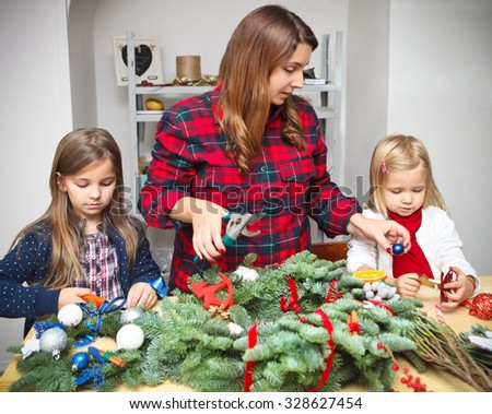 Mother making an advent wreath with the kids - dressed for the christmas