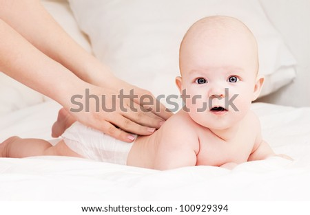 Mother massaging baby in bed at home