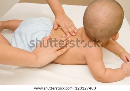 Mother massaging baby,massage back muscle