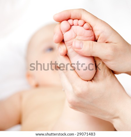 Mother massaging her child's foot, shallow focus - stock photo