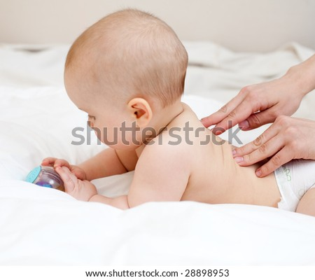 Mother massaging her child, shallow focus - stock photo