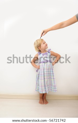 Mother measuring height of a cute child - stock photo