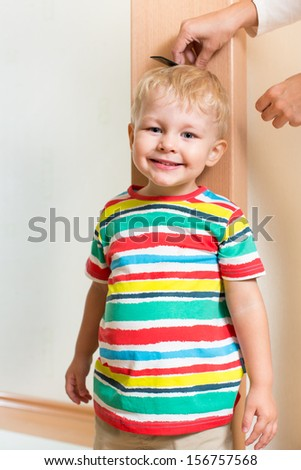 Mother measuring height of child boy - stock photo