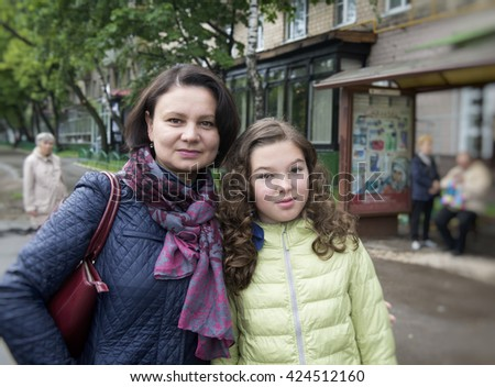 Mother (middle-aged woman) and her daughter, teenager on the street. - stock photo