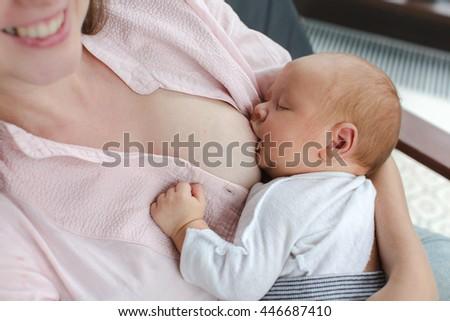 Mother nursing her newborn indoor - stock photo