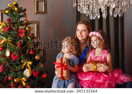 Mother of two daughters gave gifts near Christmas tree. New Year. Holiday and fun. Merry Christmas. 2017 - stock photo