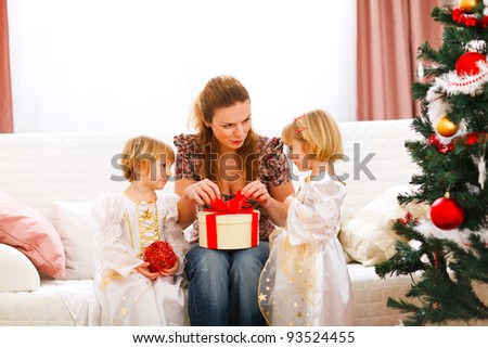 Mother opening gift presented by twins girl