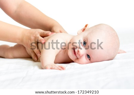 mother or massagist massaging her pleased baby