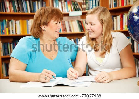 Mother or teacher helping a teenage girl study in the school library.