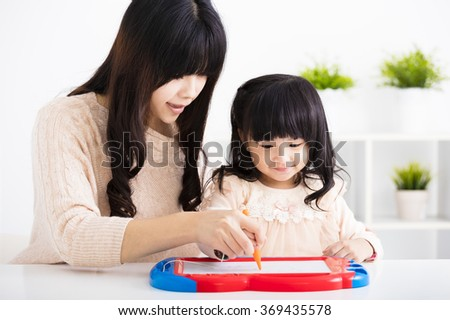 Mother or teacher helping child daughter to drawing