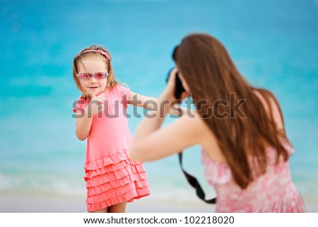 Mother photographing her daughter at tropical beach - stock photo