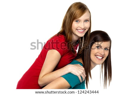 Mother piggybacks her teenage girl. All against white background. - stock photo