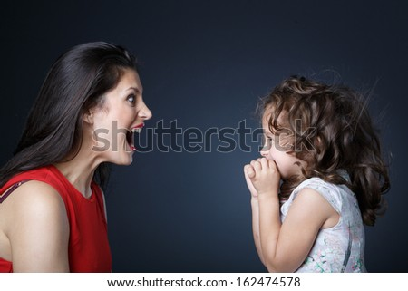 Mother playfully shouts to her daughter - stock photo