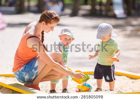 Mother playing helping two baby boys playing with sand in a sandbox - stock photo