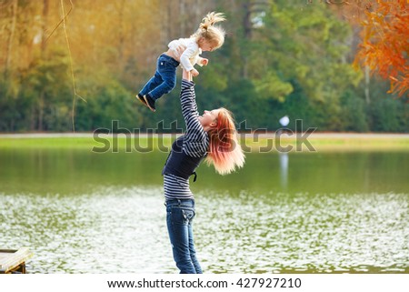 Mother playing throwing up baby girl daughter in the park lake - stock photo