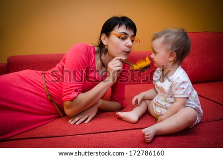 Mother playing with a baby decorative spoon and feather