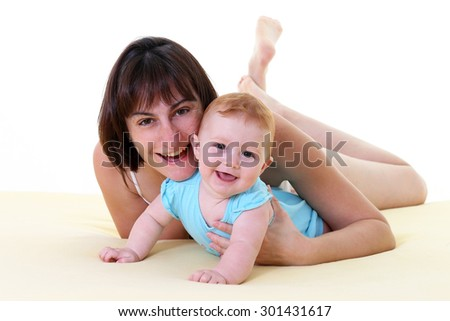 Mother playing with a baby in bed