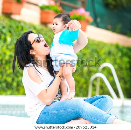mother playing with baby boy near the swimming pool on a sunny day - stock photo
