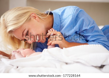 Mother Playing With Baby Girl As They Lie In Bed Together
