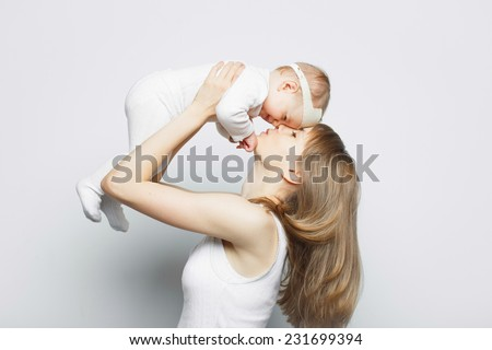 Mother playing with baby girl, happy family having fun indoor, mom and child isolated on white background. - stock photo