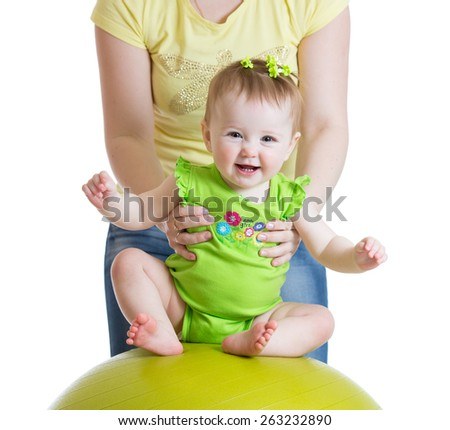 mother playing with baby girl on fitness ball